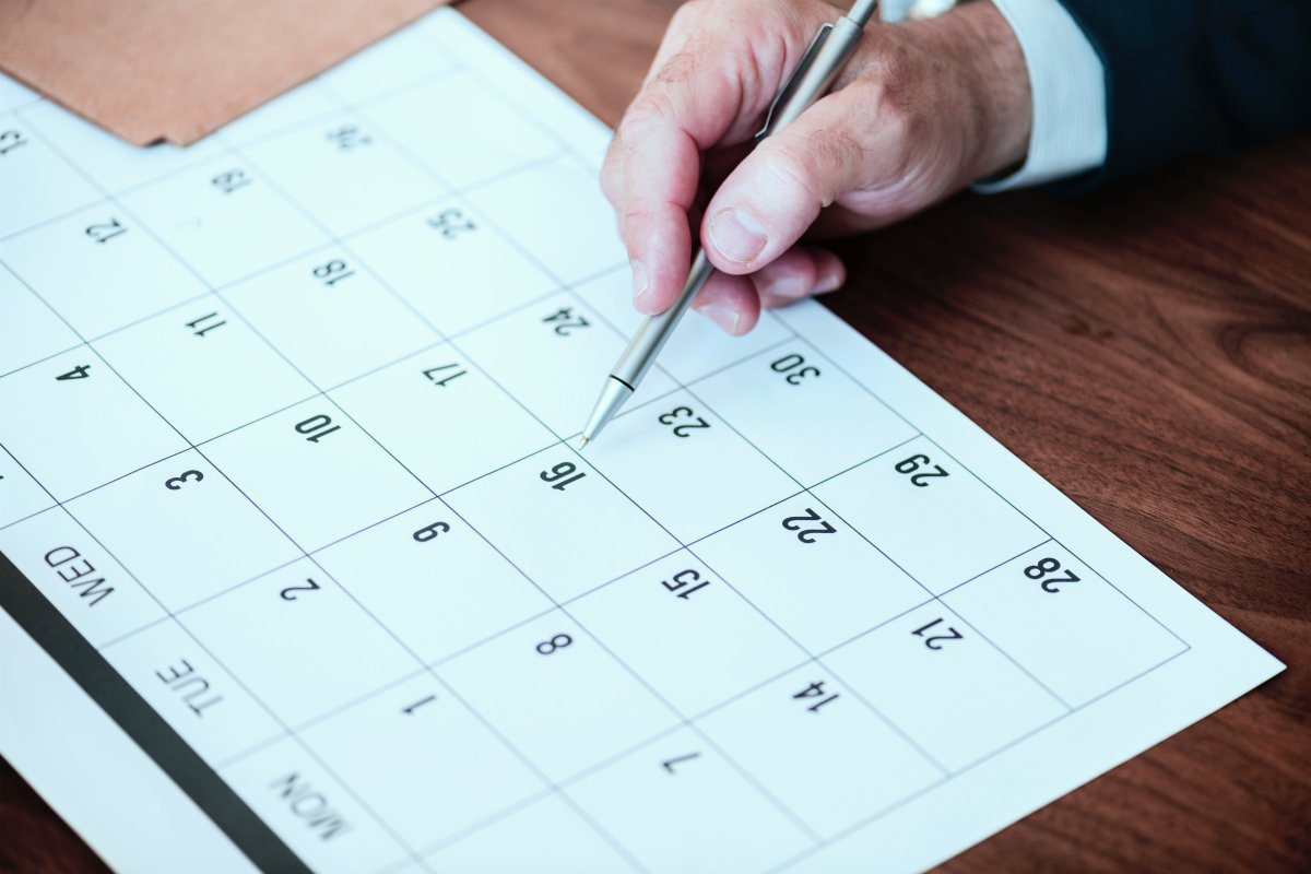 person pin pointing pen on calendar | What Happens If You Don't Pay Taxes? | Consequences and Penalties | taxes