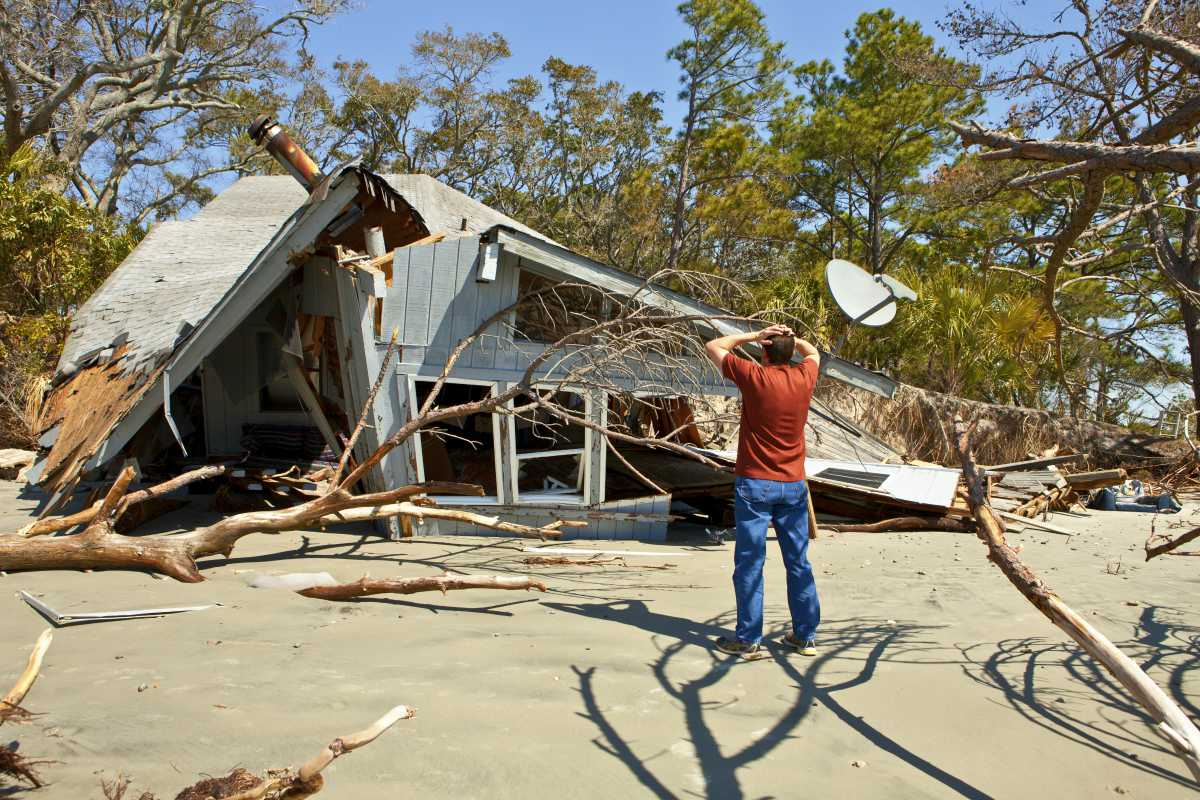 man grieving over house destroyed by flood | Tax Relief For Natural Disaster Victims | disaster tax relief