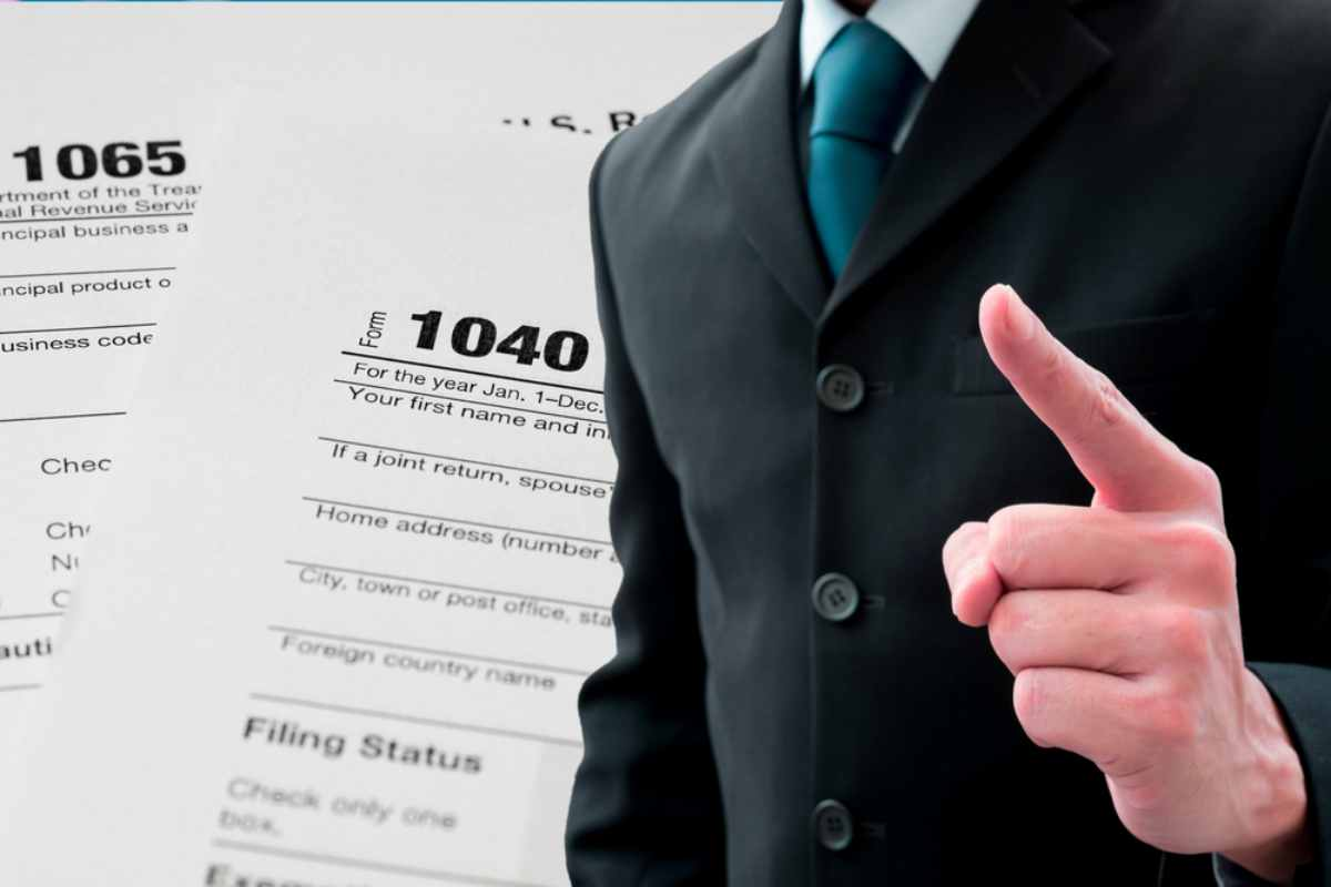 Man pointing his finger in tax form background | Things NOT To Say To The IRS If You Owe Back Taxes