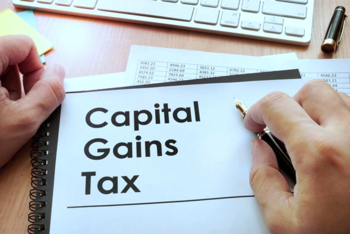 Hands holding documents title capital gains | Different Types Of Taxes We Pay In The US | IRS