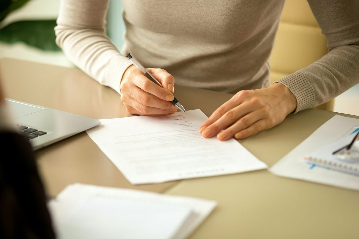 woman signing document | Using The IRS First Time Abatement Strategically To Reduce Penalties | first time abatement